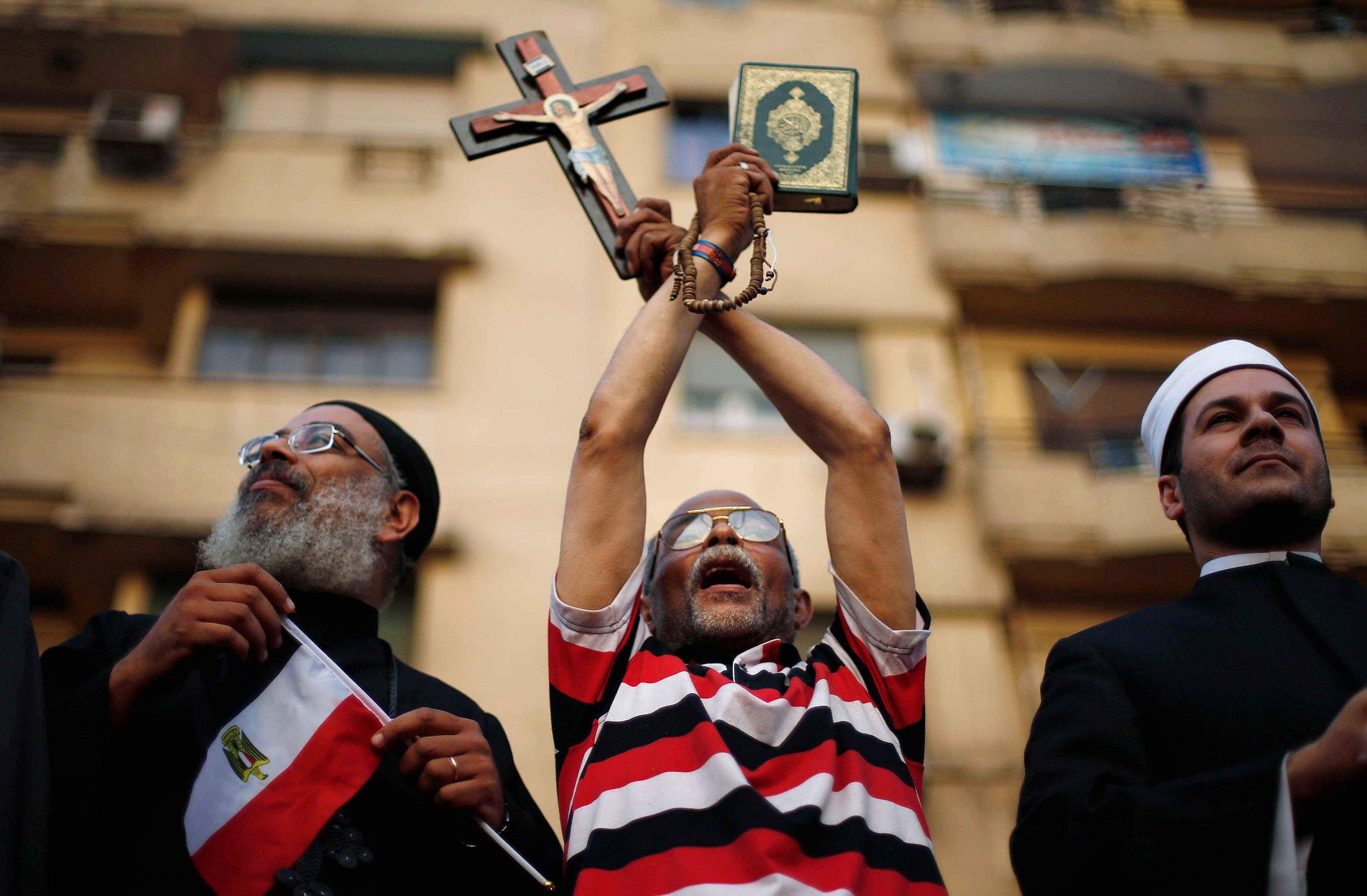 A protester holds a cross and Koran during a protest demanding that President Mohamed Mursi resign at Tahrir Square in Cairo July 1, 2013. (Reuters)