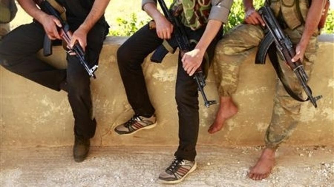Free Syrian Army members rest with their weapons on a lookout point beside the Shi'ite villages of Nubbul and Al-Zahraa that they plan to siege in Aleppo countryside June 30, 2013. (Reuters)