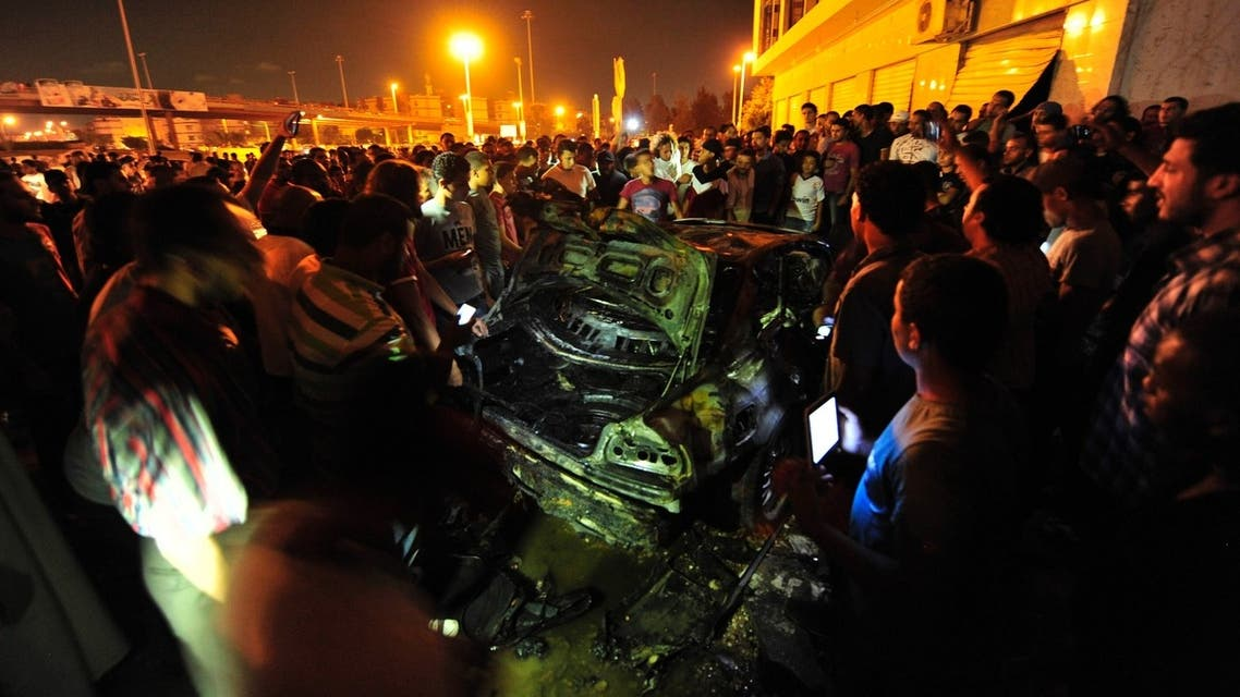 Onlookers gather around the wreckage of a car, which exploded near members of a special forces unit, in Benghazi, July 3, 2013.