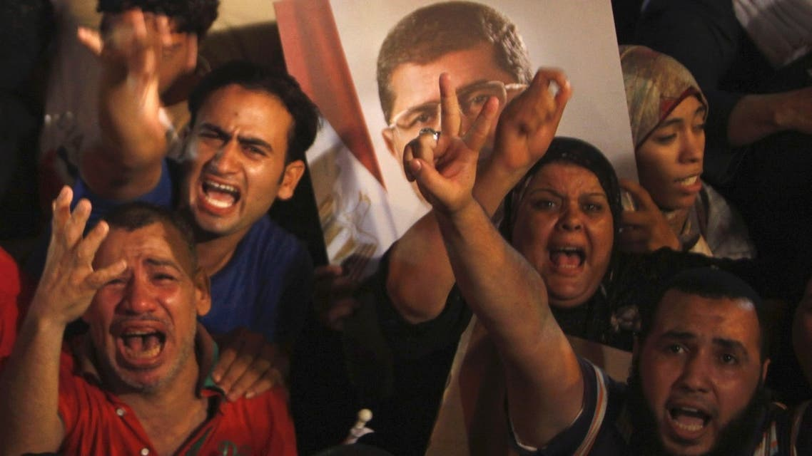 Supporters of Egypt's President Mohamed Mursi react after the Egyptian army's statement was read out on state TV, at the Raba El-Adwyia mosque square in Cairo July 3, 2013. Reuters