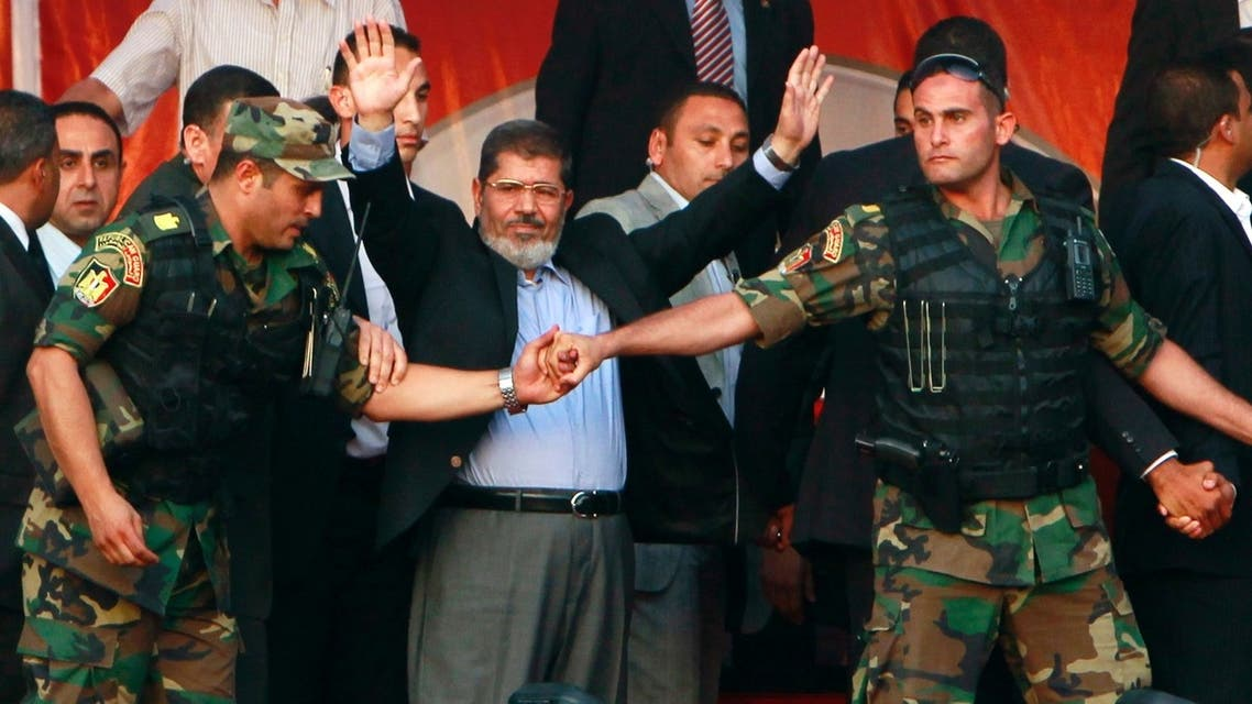 Only a year ago: Egypt's then President-elect Mohammed Mursi waves to his supporters while surrounded by members of the presidential guard in Cairo's Tahrir Square on June 2012. (Reuters)
