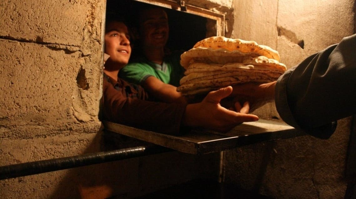 Syrian men line up to buy bread at the only bakery still open in the city of Al-Bueda. (AFP)