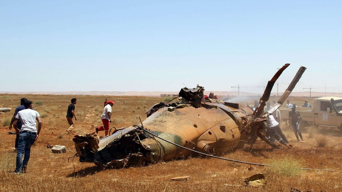 Libyan emergency personnel inspect the wreckage of a military helicopter that crashed during an airshow in the eastern city of Benghazi on July 4, 2013. AFP