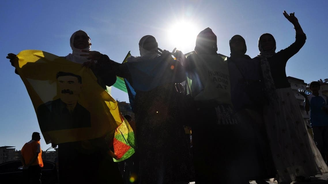 Kurds dance with a picture of PKK (Kurdistan Workers Party) jailed leader Abdullah Ocalan during a protest on June 30, 2013, in Diyarbakir. AFP