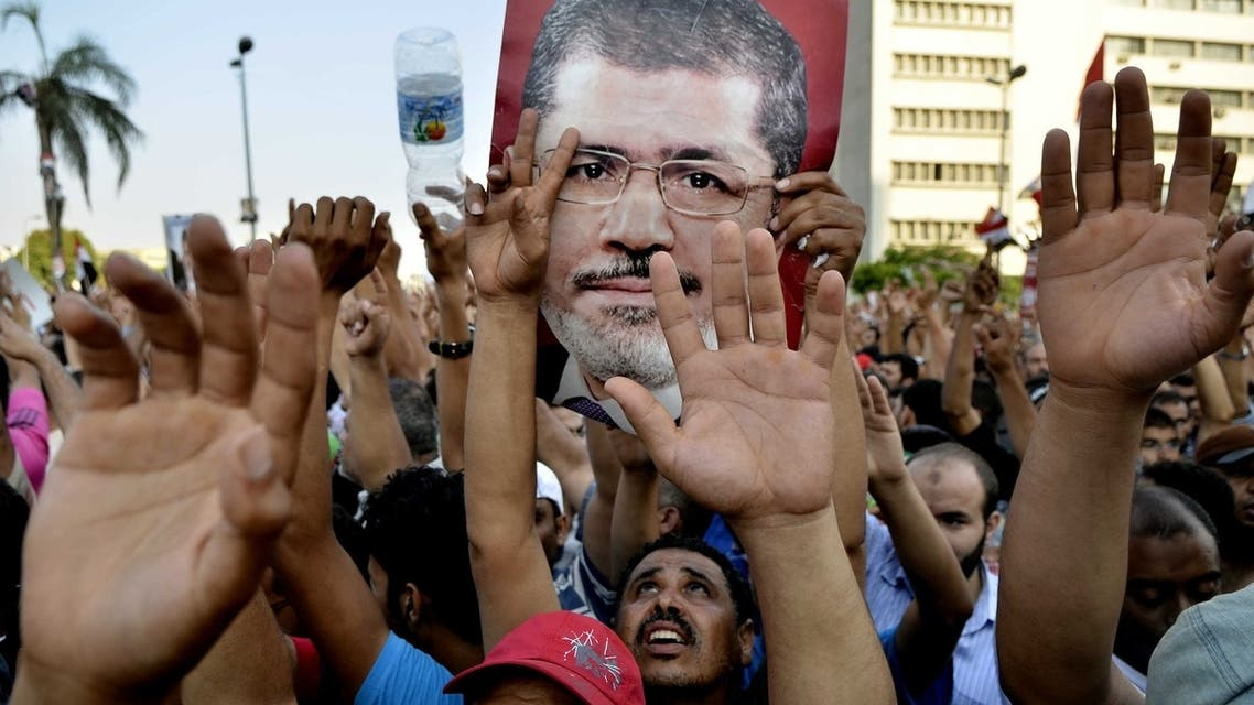 Egyptian supporters of the Muslim Brotherhood hold pictures of deposed president Mohamed Mursi as they shout slogans during a demonstration outside the Republican Guards headquarters in Cairo on July 5, 2013. (AFP)