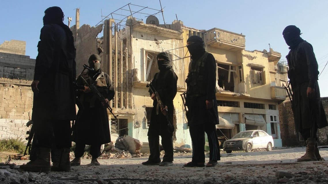 Free Syrian Army members accompanied by fighters from the Islamist Syrian rebel group Jabhat al-Nusra carry their weapons as they stand in front of a damaged building in the old city of Homs July 2, 2013.