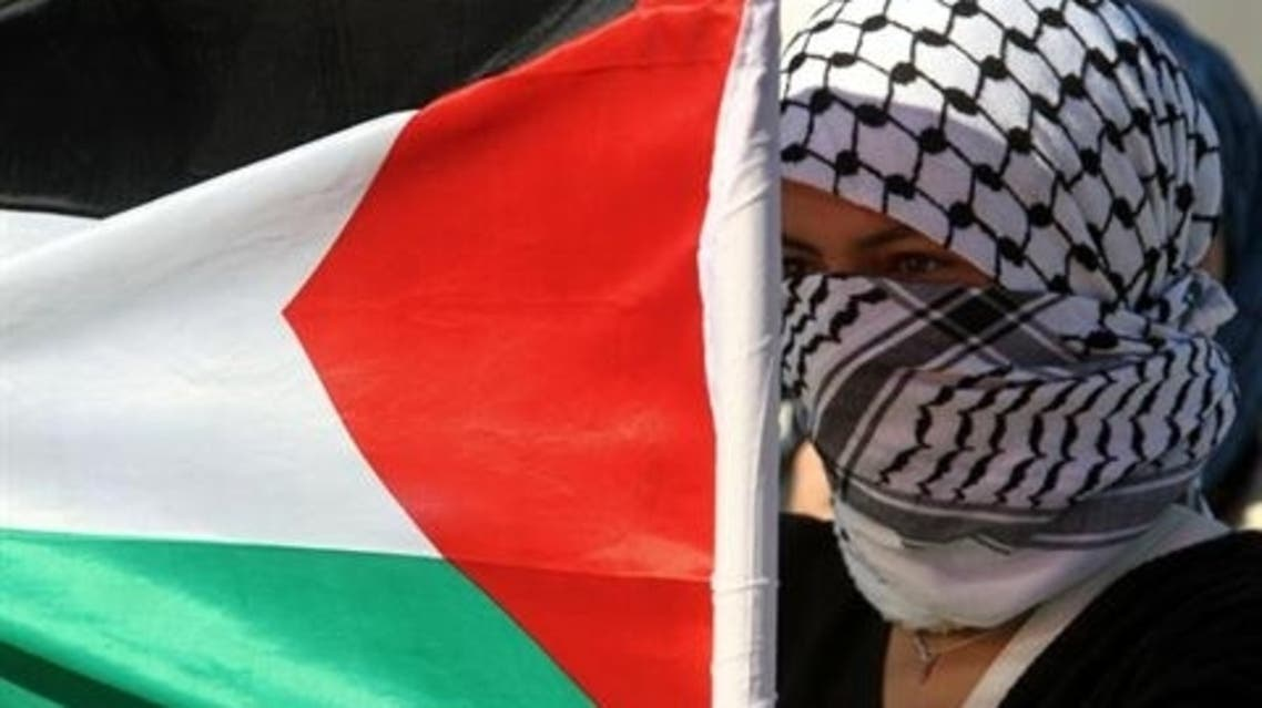 A masked Palestinian youth holds her national flag near Israeli soldiers (unseen) during a protest denouncing Israel's ongoing military operation in the Gaza Strip, on November 15, 2012, in the West Bank city of Nablus.AFP