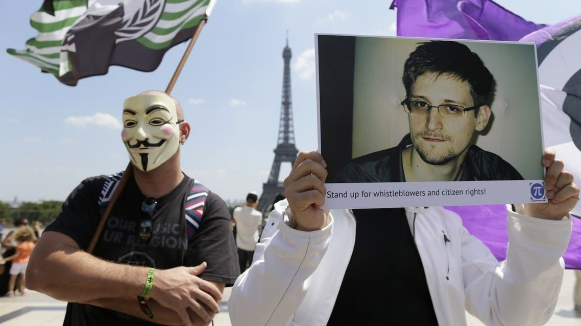 demonstrator holds up a picture of the former technical contractor of the US Central Intelligence Agency Edward Snowden during a demonstration in support of Snowden at the Place du Trocadero in front of the Eiffel tower in Paris on July 7, 2013.