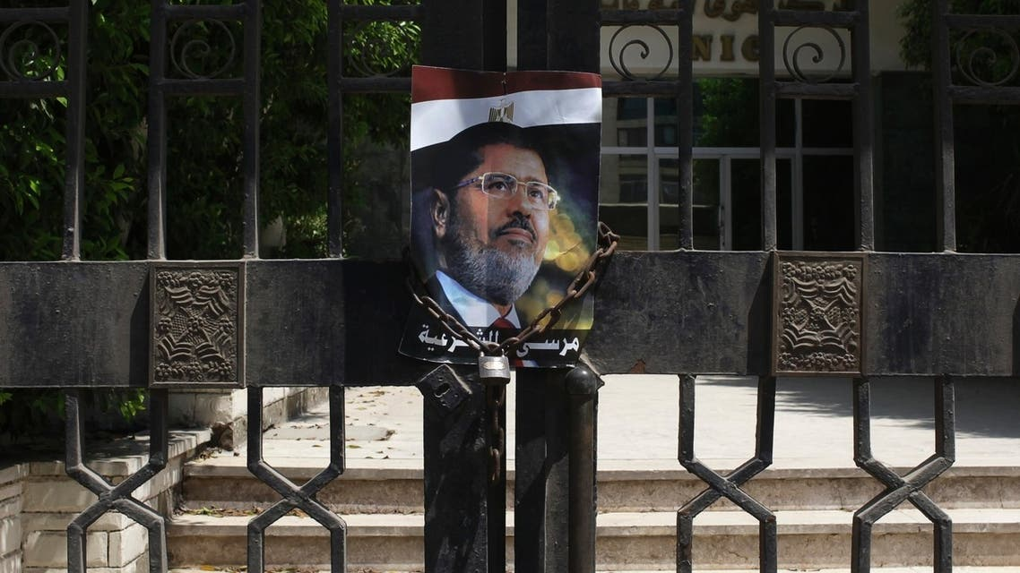 A picture of deposed Egyptian President Mohamed Mursi is chained on the gates outside a government building near the Republican Guard headquarters in Cairo July 7, 2013. (Reuters)