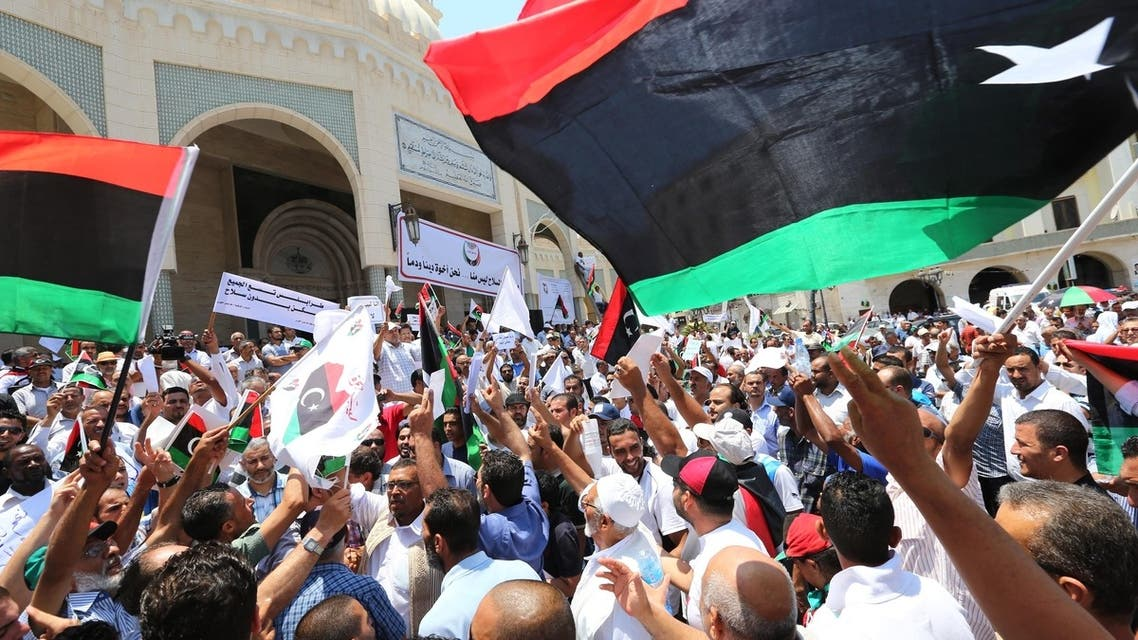 Libyan protesters shout slogans waving national flags during a demonstration on the Algeria Square to demand the removal of arms and the evacuation of unofficial armed groups and the implementation of the General National Congress (GNC)'s decision on July 7, 2013 in the Libyan capital Tripoli. (AFP)