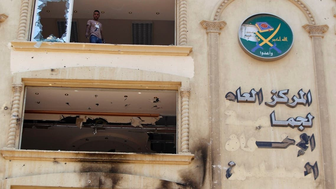A looter stands near a broken window at the Muslim Brotherhood's headquarters after it was burned down by protesters opposing Egyptian President Mohamed Mursi in Cairo's Moqattam district in this July 1, 2013 file picture.
