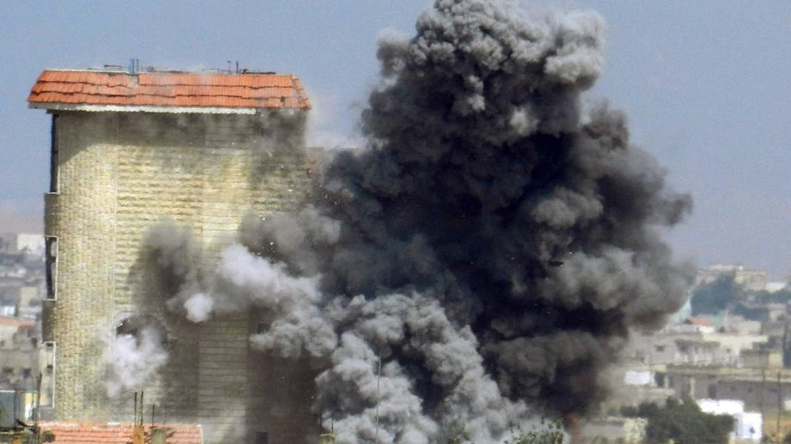 A handout picture released by the opposition-run Shaam News Network on June 2, 2013, shows smokes rising as a mortar shell hits a building in the town of al-Hula in the Syrian province of Homs. (File photo: AFP)