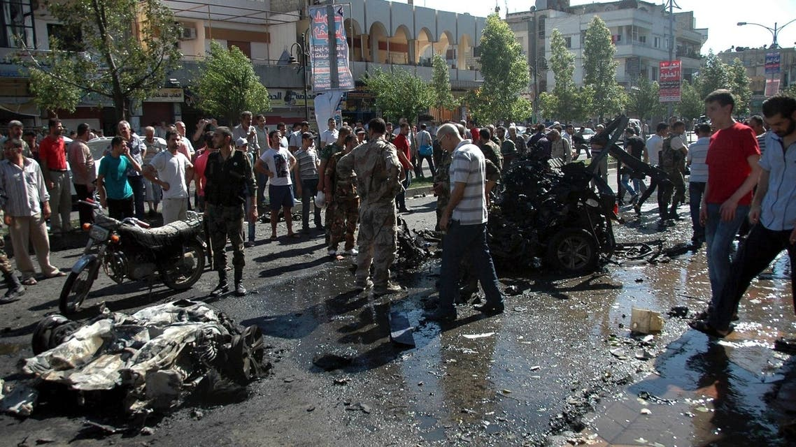 People stand at the site of an explosion in Ekrema neighbourhood in Homs city July 8, 2013, in this handout photograph released by Syria's national news agency SANA. Reuters