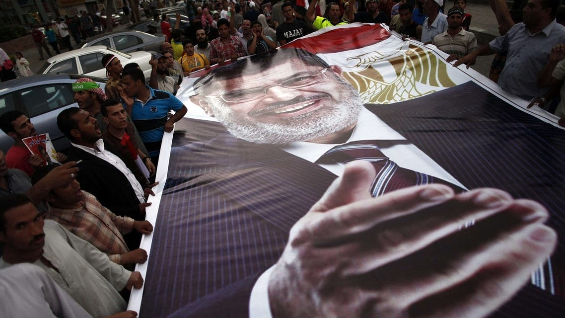 Ousted President Mohamed Morsi supporters and Muslim Brotherhood members hold a giant portrait of him as they demonstrate against his toppling at Raba al-Adwyia mosque on July 7, 2013 in Cairo. AFP