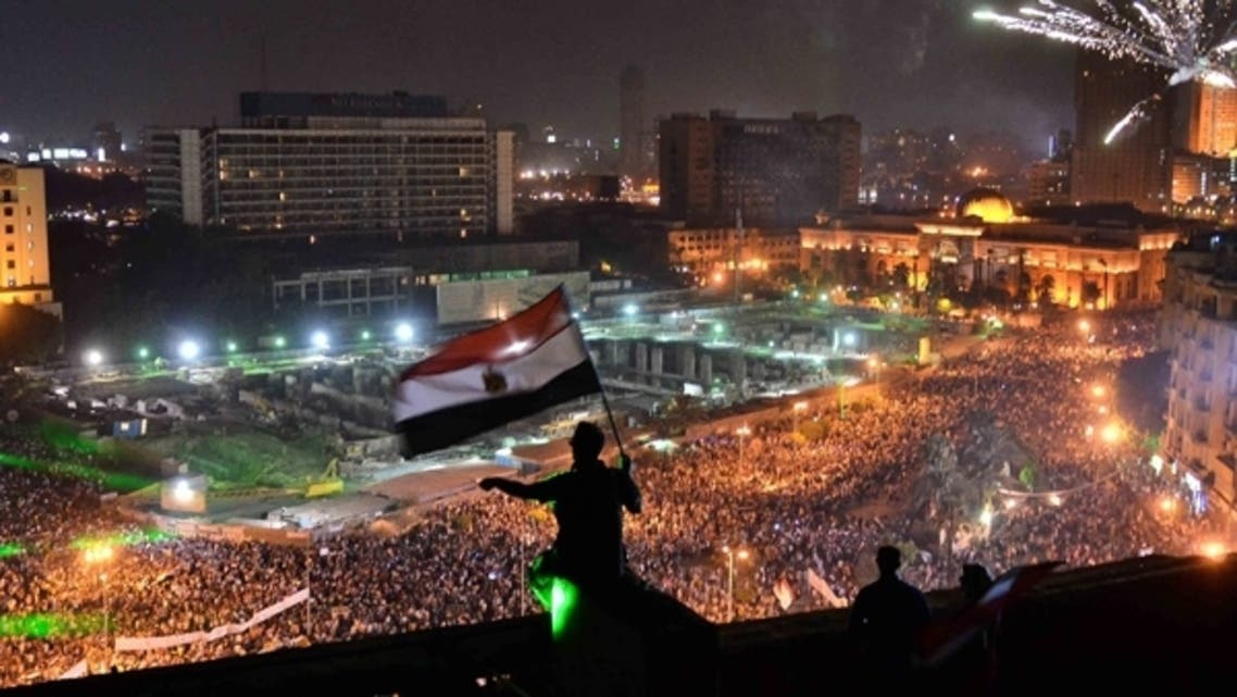 Egyptians wave the national flag on a building rooftop on July 7, 2013 as hundreds of thousands flood Egypt's landmark Tahrir square to demonstrate against ousted President Mohammad Mursi. (AFP)