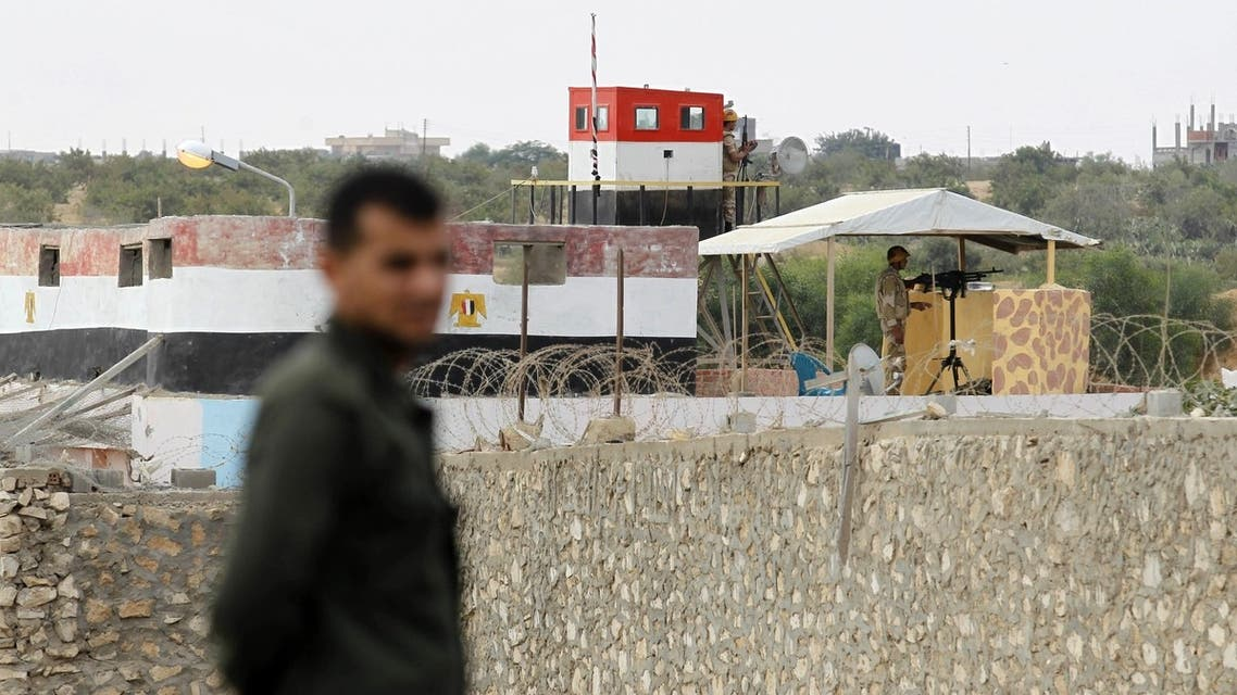 A Hamas policeman (L) stands in Rafah in the southern Gaza Strip on the border with Egypt, on July 8, 2013, while Egyptian soldiers standing on top of a watch-tower keeps watch from the Egyptian side of the border. AFP