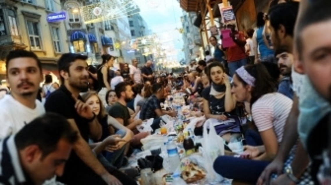 Turkish anti goverment protesters gather as they break their first day of fasting for the Muslim holy month of Ramadan on Istiklal street, the main shopping corridor, on July 9, 2013 in Istanbul. (AFP)