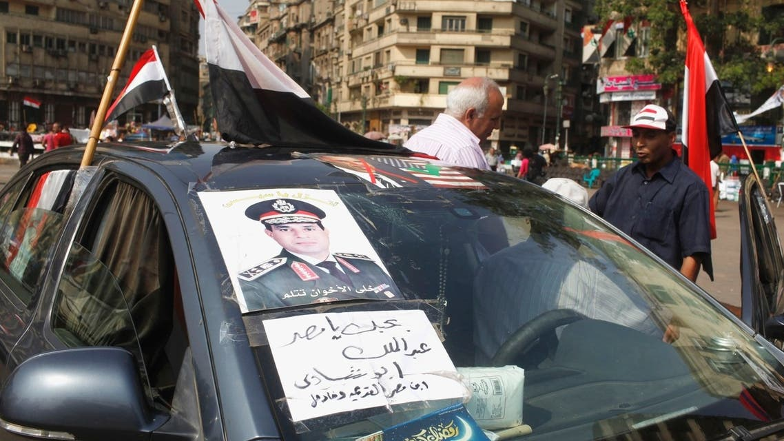 """A man with a poster of the chief of Egypt's armed forces General Abdel Fattah al-Sisi on his car, talks to a protester in Tahrir square, in Cairo, July 9, 2013. Sign reads, """"I love Egypt."""" (Reuters)"""
