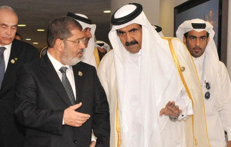 Ousted Egyptian President Mohammad Mursi (L) speaks with former Qatari leader Emir Sheikh Hamad bin Khalifa al-Thani during the 16th summit of the Non-Aligned Movement in Tehran, 30 August 2012. (File Photo: Reuters)