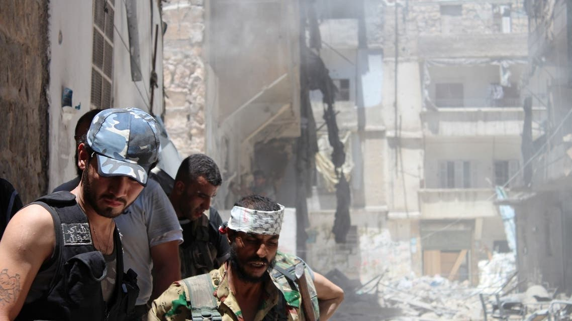 Syrian rebels gather outside a building which they blew up to target a regime sniper taking shelter inside but who managed to escape in the Salaheddine district of the northern city of Aleppo on July 10, 2013. (File photo: AFP)