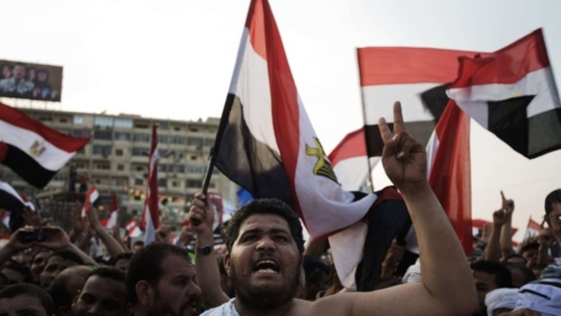 Muslim Brotherhood members and supporters of deposed president Mohammed Morsi shout slogans waving national flags during a rally outside Rabaa al-Adawiya mosque on July 15, 2013 in Cairo, Egypt. (Reuters)