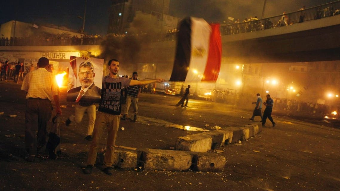 A supporter of deposed Egyptian president Mohamed Mursi holds up his poster and a national flag during clashes between the police and Mursi supporters in the Ramsis square area in central Cairo July 15, 2013. (Reuters)