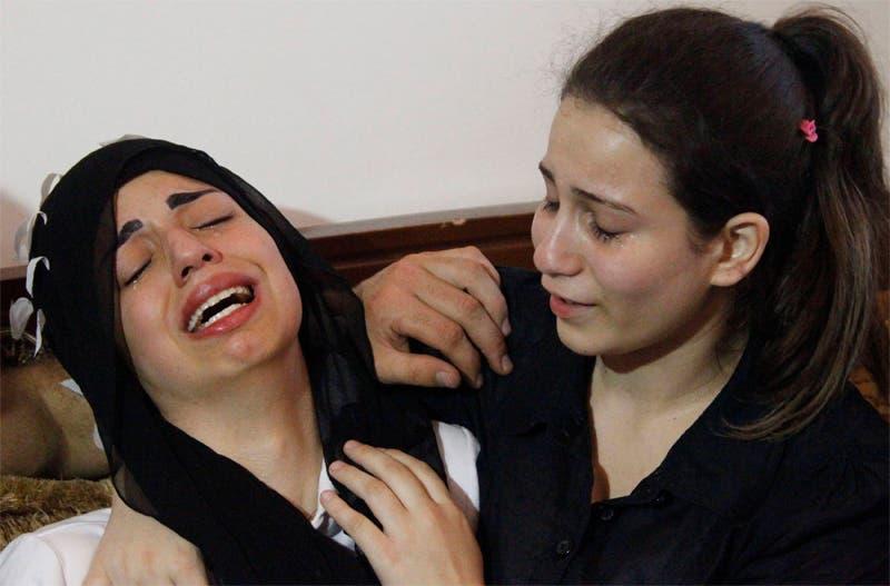 فاطمة محمد ضرار جمو (يسار) تبكي والدها بعد اغتياله