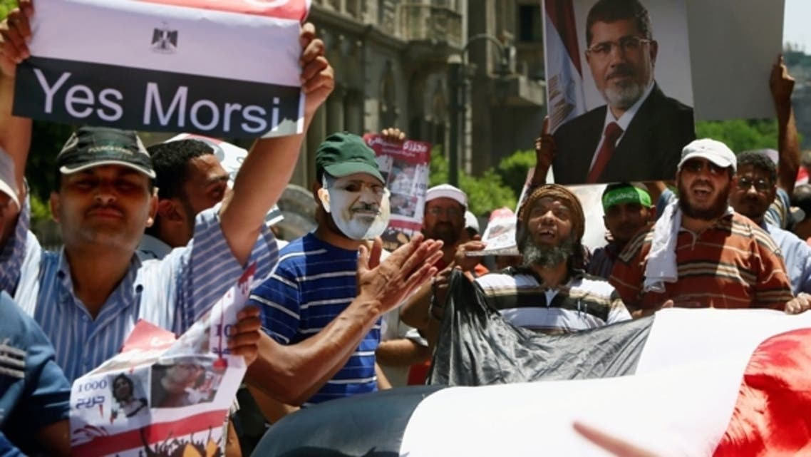Supporters of Muslim Brotherhood and Egypt's ousted president Mohammad Mursi (on posters) raise up placards and deploy a giant national flag during a rally on the road leading to the government headquarters on July 17, 2013. (Reuters)