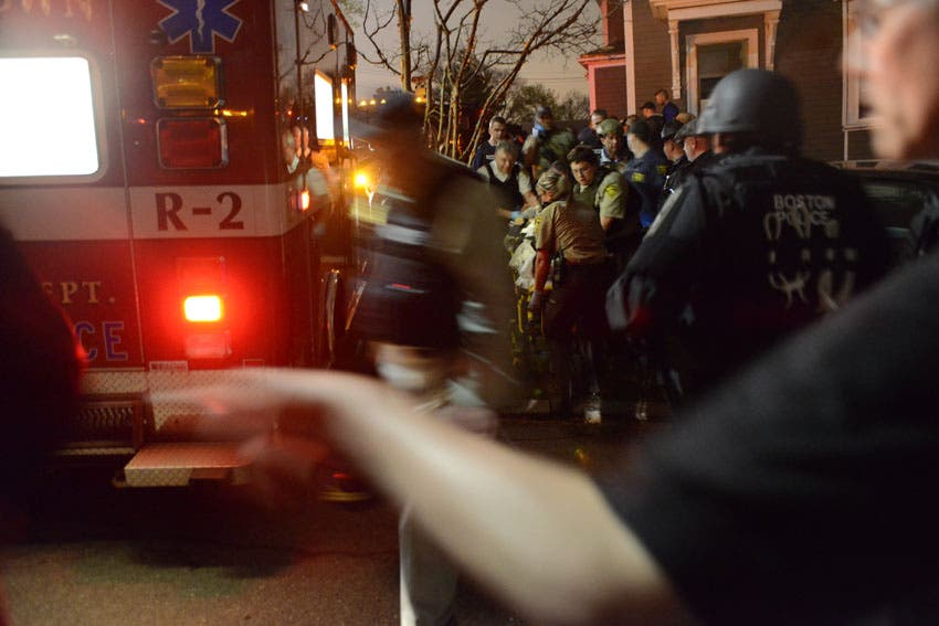 After his arrest, medical personnel rush Tsarnaev to the ambulance. (Photo courtesy: Sean Murphy/Boston Magazine)