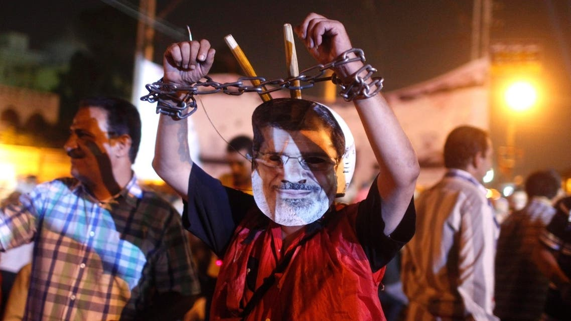 An anti-Mursi protester wears a mask depicting deposed president Mohamed Mursi, and chains on his hands, close to the presidential palace in Cairo July 19, 2013.