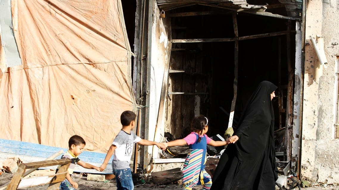 A family walks past the site of a car bomb attack at the neighbourhood of Tobchi in Baghdad, July 21, 2013. (Reuters)