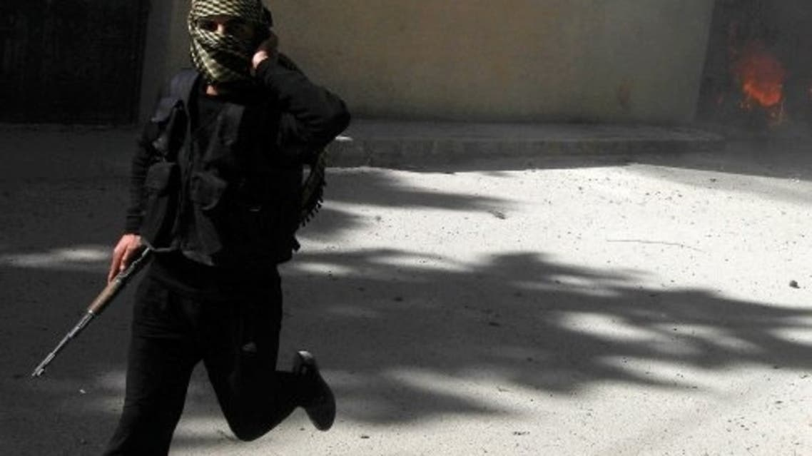 A fighter from Islamist Syrian rebel group Jabhat al-Nusra runs with his weapon as their base is shelled in Raqqa province, eastern Syria, March 14, 2013. (Reuters)