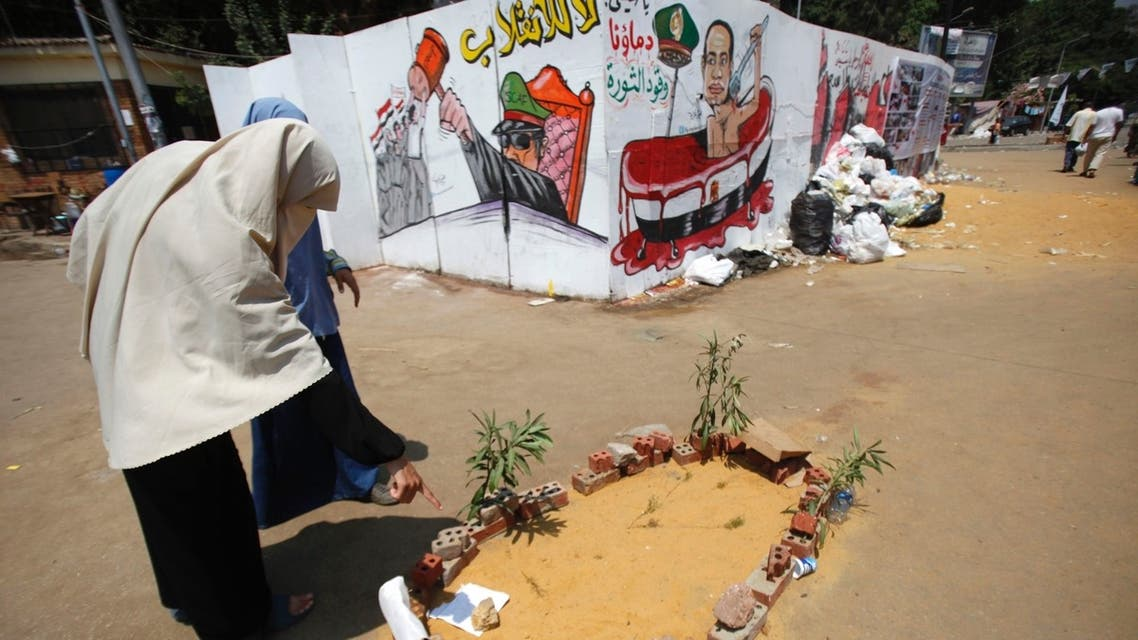 Members of the Muslim Brotherhood and supporters of ousted Egyptian President Mohamed Mursi walk near the mock grave of a protester who was killed yesterday, during clashes around Cairo University and Nahdet Misr Square in Giza July 23, 2013.