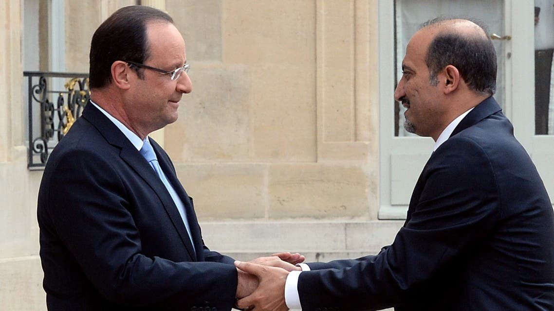 Syria's new opposition leader Ahmad Jarba (R) shakes hand with France President François Hollande as he arrives for a meeting at the Elysee presidential palace on July 24, 2013 in Paris. (AFP)