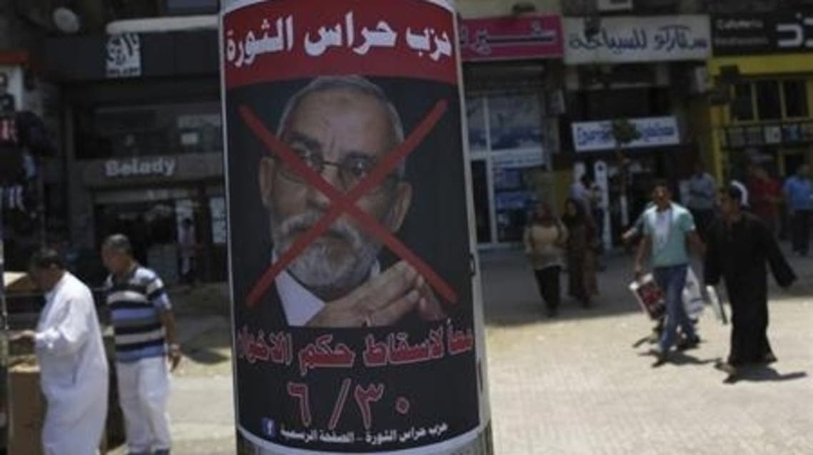 "People walk past a defaced poster of Muslim Brotherhood leader Mohammad Badie with Arabic text which reads ""Together to down brotherhood's power"" near Tahrir Square in Cairo June 23, 2013. (File Photo: reuters)"