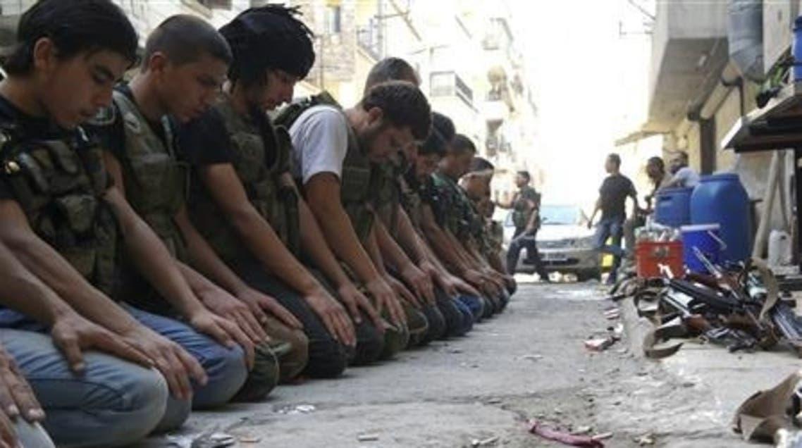 FSA fighters pray (Reuters)