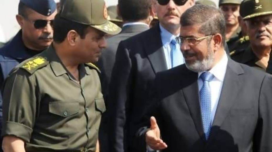 Egypt's ousted President Mohammed Mursi (right) speaks with defense minister, General Abdel Fattah el-Sisi, during a visit to the 6th Armoured Division near Ismailia on October 10. (File Photo: Reuters)