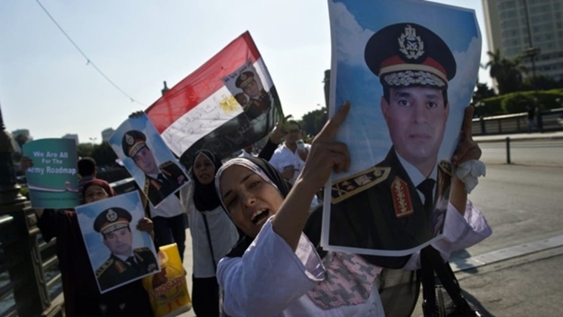 Supporters of army chief General Abdel Fattah al-Sisi carry his portrait and wave the Egyptian flag in Cairo's Tahrir square on July 16, 2013.  (AFP)