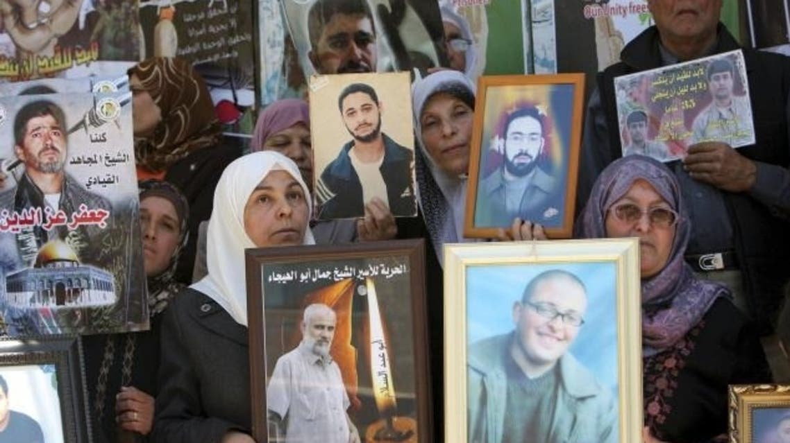 In this April 17, 2012 photo, Palestinians hold photographs of prisoners jailed in Israel, during a rally marking the annual prisoners' day in the West Bank  AP