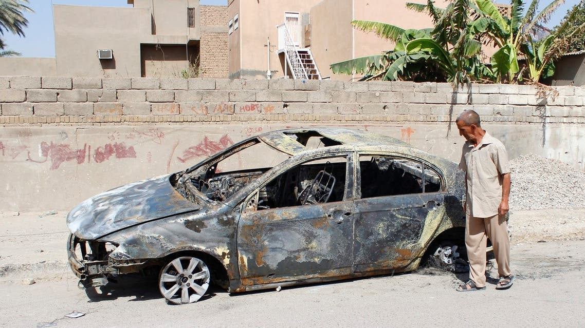 A man looks at a damaged vehicle after a bomb attack last night in Baghdad, July 28, 2013.
