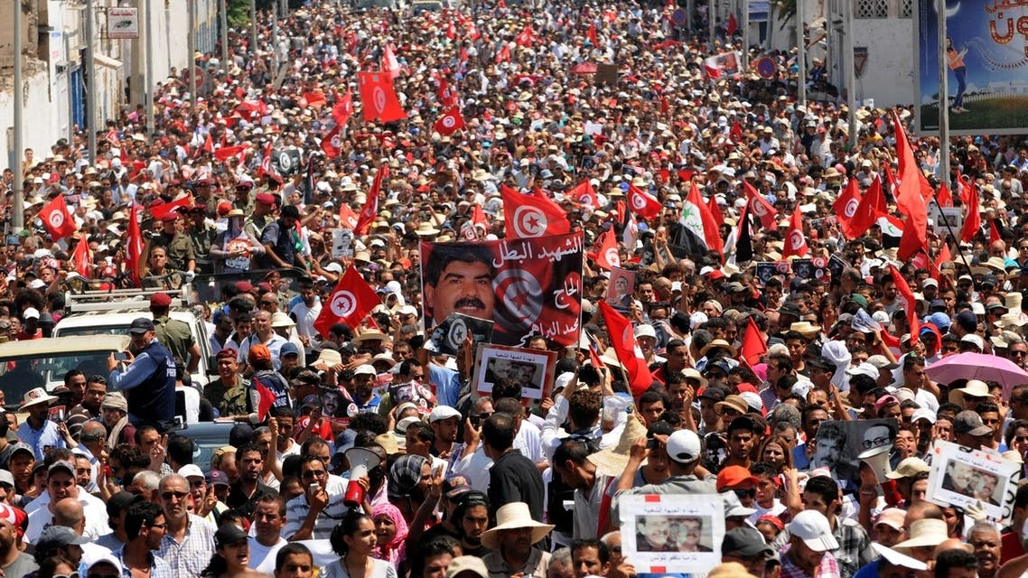 Tunisians join the funeral procession of opposition leader Mohammad al-Brahimi after it left his home in the Tunis suburb of Ariana on July 27, 2013. (AFP)