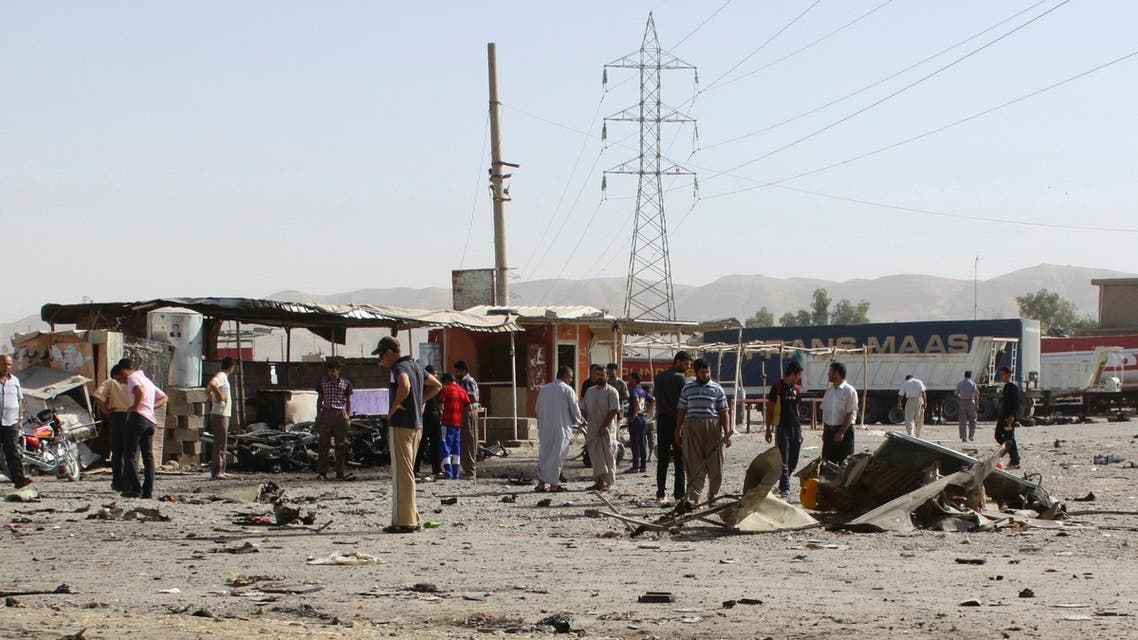 Residents gather at the site of a suicide bomb attack in Tuz Khurmato, 170 km (105 miles) north of the Iraqi capital Baghdad, July 28, 2013. (Reuters)
