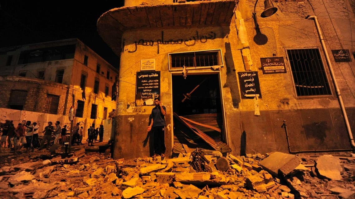 A man talks on his mobile phone while standing on debris after explosions at judicial buildings in Benghazi July 28, 2013.