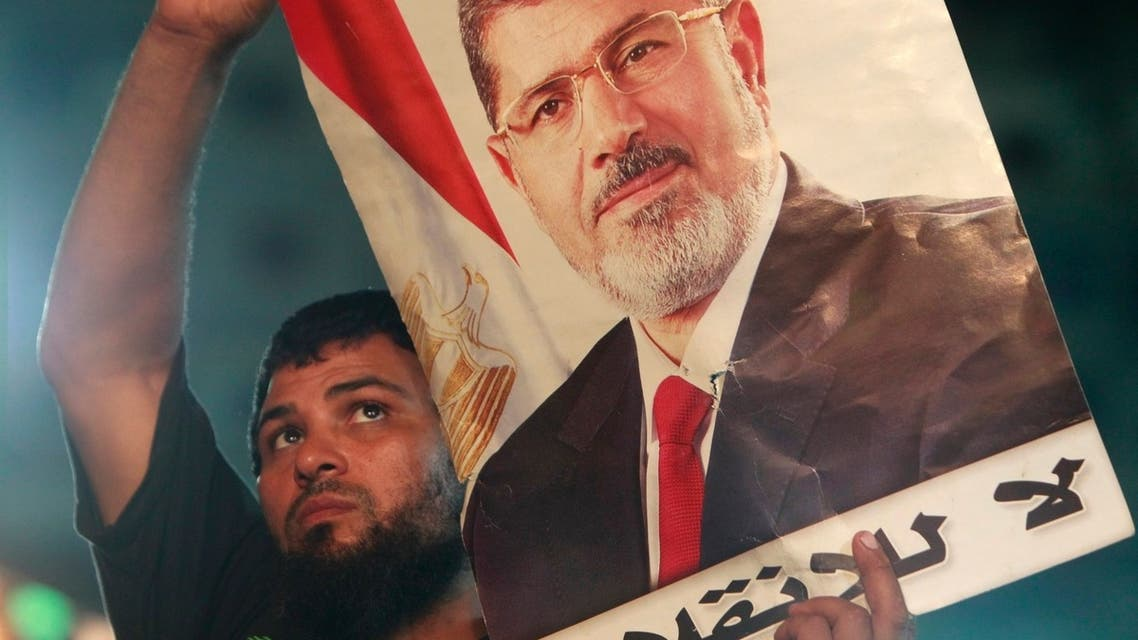 A supporter of deposed Egyptian President Mohamed Mursi carries a Mursi poster during a protest at the Rabaa Adawiya square, where Mursi supporters are camping, in Cairo July 27, 2013.