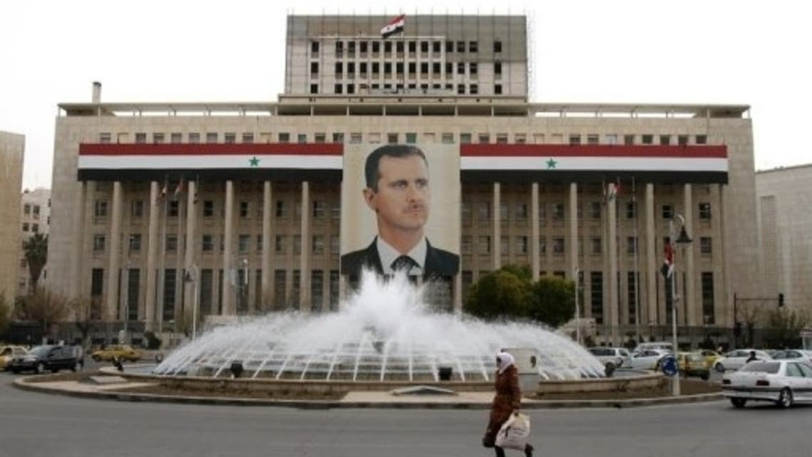 A woman walks past the central bank building decorated with a banner of Bashar al-Assad in Damascus on February 28, 2012. (File Photo:AFP)