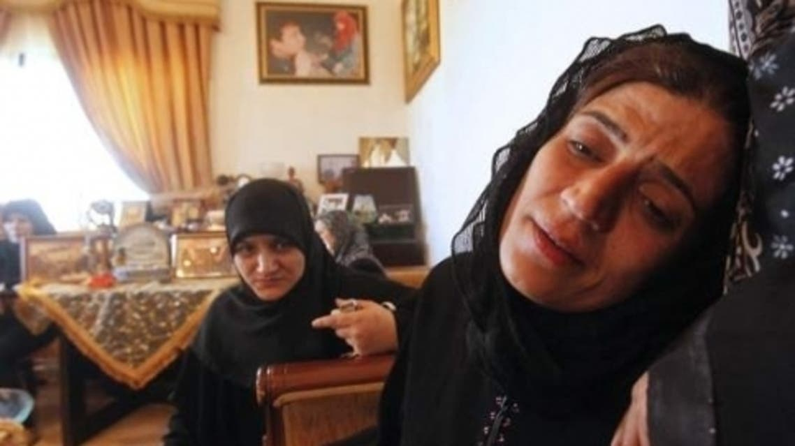 Siham, wife of Mohammad Darro Jamo, mourns his death as she is comforted by a relative in Sarafand, southern Lebanon July 17, 2013. (Reuters)