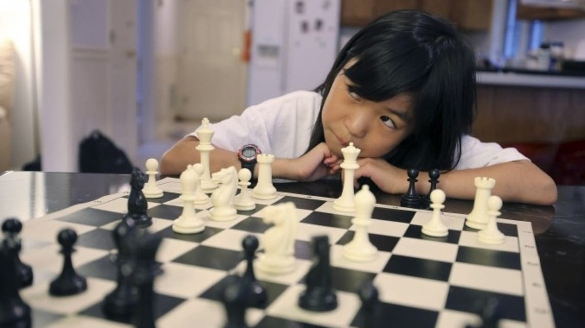 Carissa Yip, 9, waits for her father Percy Yip to make a move during a chess match at their home in Chelmsford, Mass. (Photo Courtesy: The Associated Press)