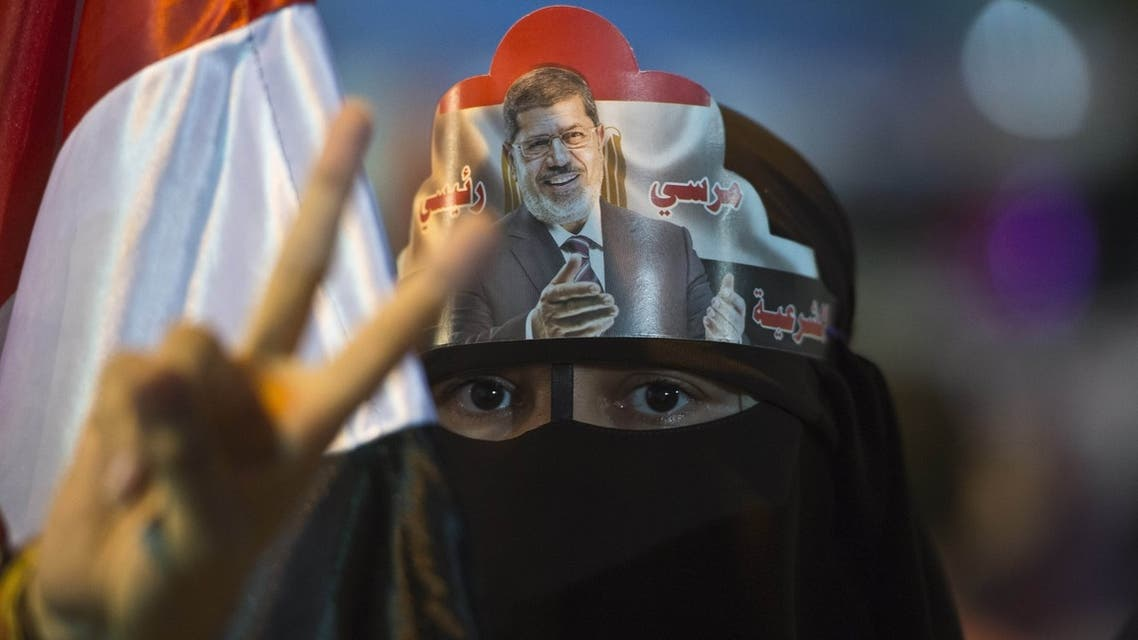 A female supporter puts Egypt's deposed president Mohamed Morsi portrait on her head during sit in outside Rabaa al-Adawiya mosque in Cairo on August 1, 2013. AFP