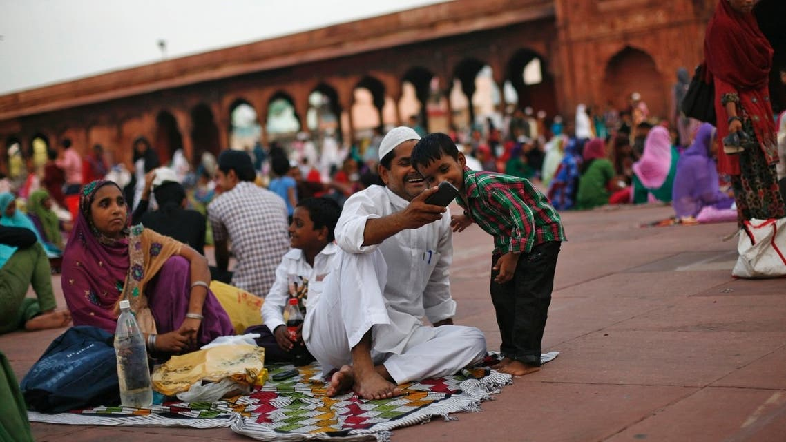 A Muslim boy looks at a mobile phone before having his iftar (breaking fast) meal during the holy month of Ramadan at the Jama Masjid (Grand Mosque) in the old quarters of Delhi August 1, 2013. Reuters