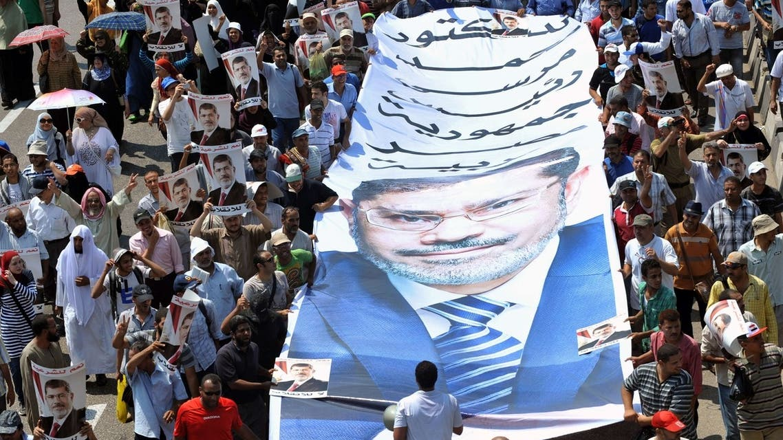 Egyptian supporters of the deposed president Mohamed Mursi carry a giant poster bearing his portrait during a demonstration against the government in Cairo on August 2, 2013. (AFP)
